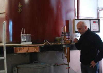 Distillateur dégustant son eau-de-vie de cognac pendant la distillation